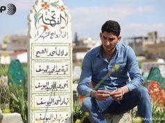 عبدالحميد اليوسف بجانب قبر ولديه - المصدر: AFP