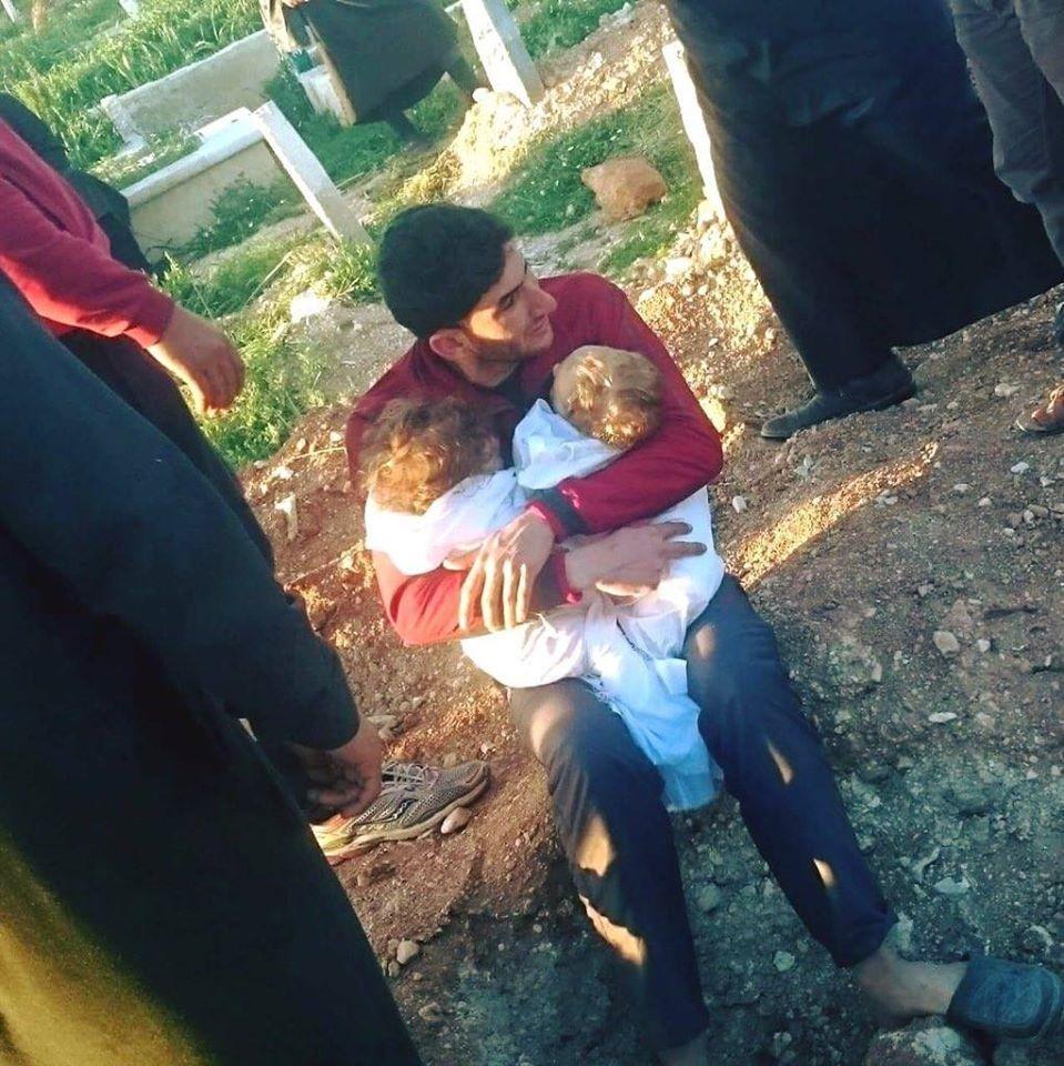 عبد الحميد اليوسف مع أطفاله التوأم بعد وفاتهما في مجزرة خان شيخون-انترنت