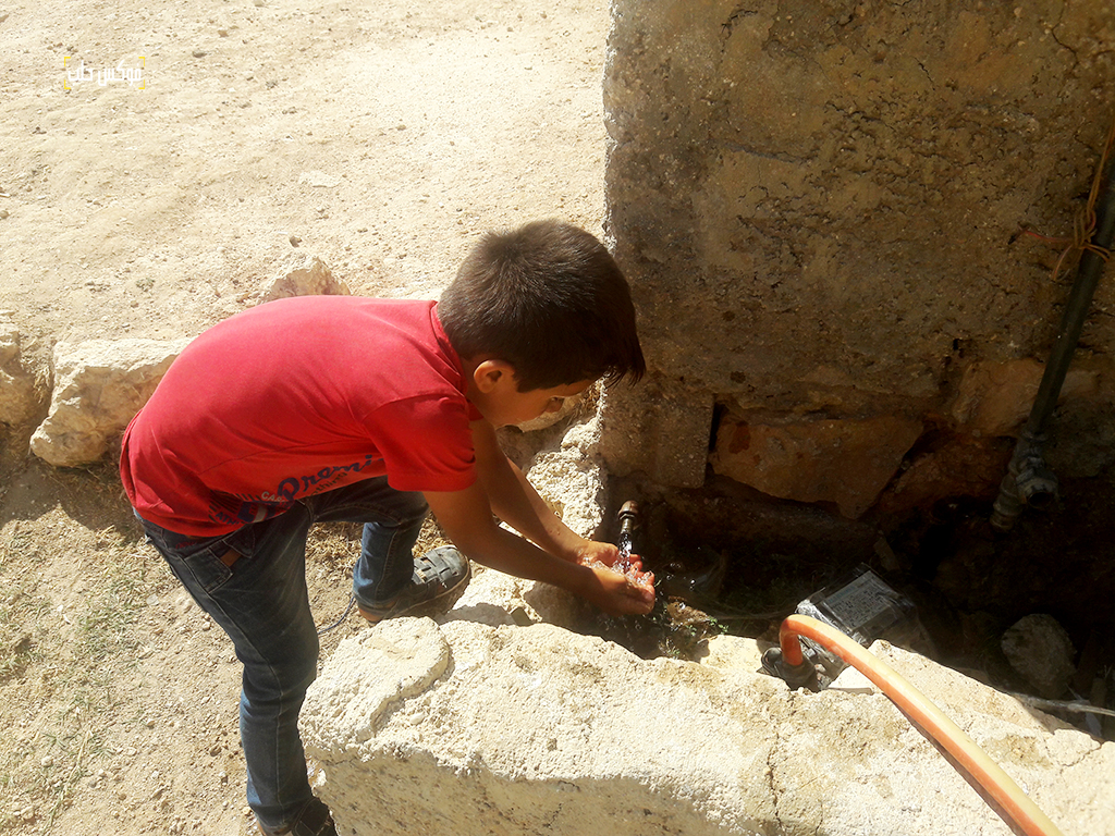 طفل في قرية تركمان بارح يشرب من منهل المياه العام مباشرة