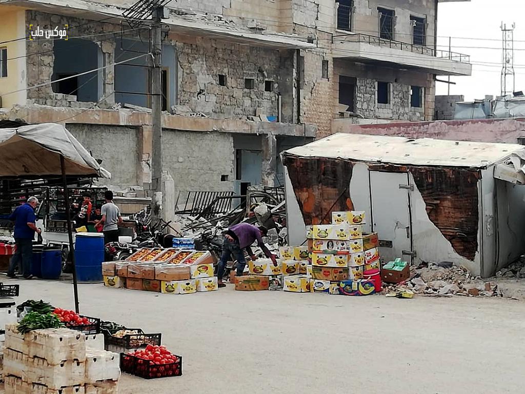 بسطات في سوق الأتارب وتظهر خلفها البيوت المدمرة بفعل القصف