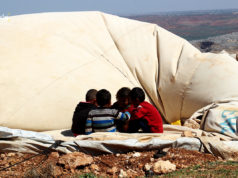 أطفال يجلسون على خيمتهم بعد أن هدمتها العاصفة الهوائية في مخيم كفتين بريف إدلب