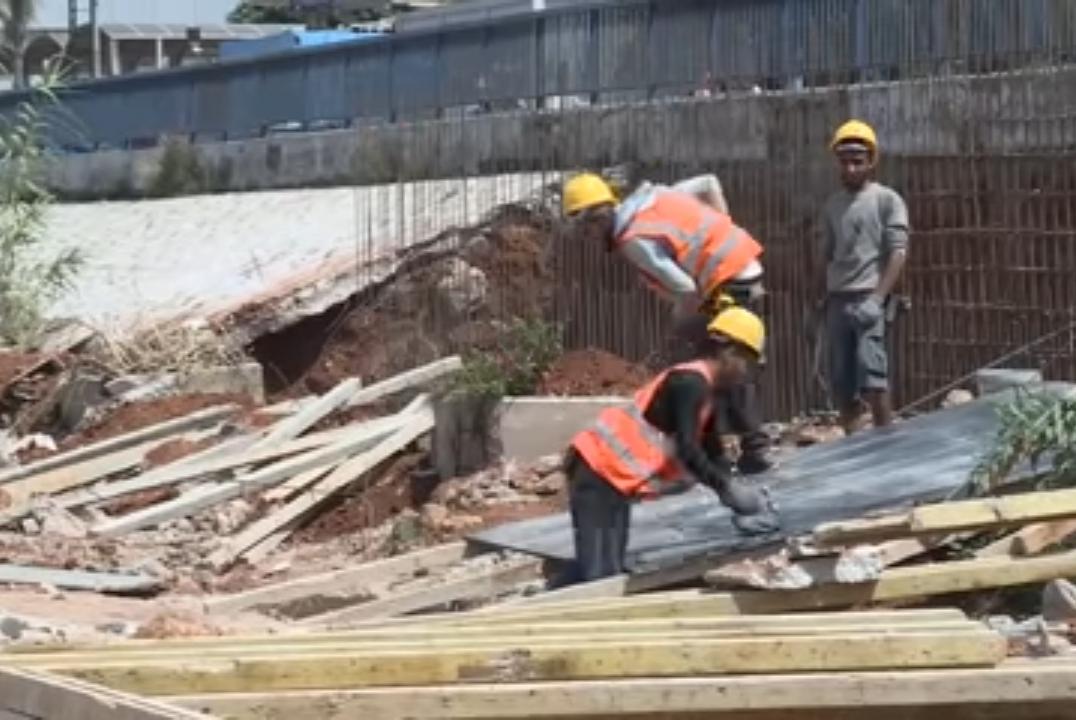 عمال سوريون بينهم عمر عبد المحسن يعملون في ورشة بناء -فوكس حلب