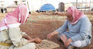 الحاج علي وخليل يلعبان الادريس بالقرب من خيمتهما -فوكس حلب