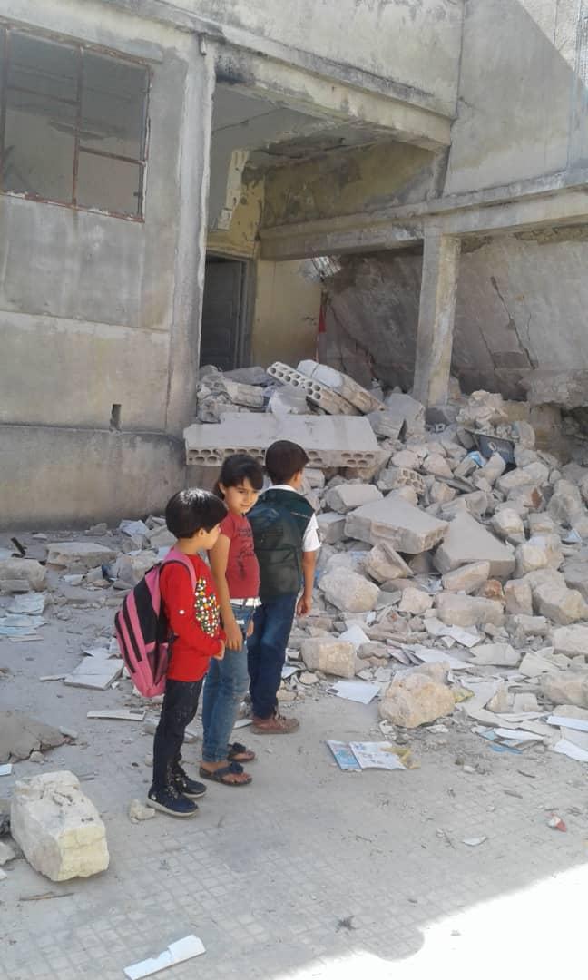 أطفال يمرون من أمام مدرستهم المدمرة في قرية المغارة بجبل الزاوية